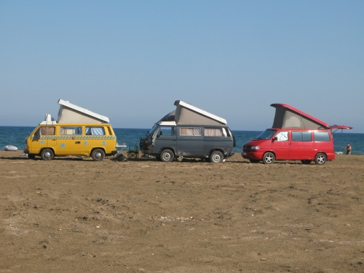 A couple of T3 & a T4 campervans on a beach camp site.